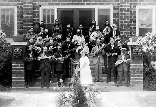 Mid-1930s, musicians on the front step of Shiloh, administration building, Mary's City of David. The Clark Irish Harp, built in 1914, ar Syracuse, NY, is restored and is resident at the 200 Years Library at Shiloh, and is played by our youngest member, Carl Payne.