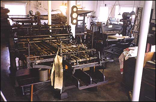 Interior of Printshop, center is a folding machine, the press in the rear is from 1891.